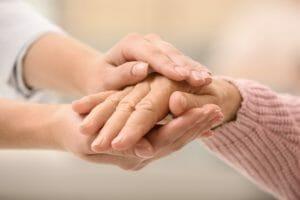 image d'une personne prenant par la main une autre personne visiblement plus âgée
