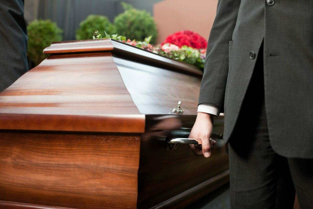 image représentant un homme portant un cercueil lors de la mise en bière